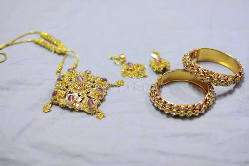Fermez-vous vers le haut des bijoux brillants d'or sur le tissu blanc photos libres de droits