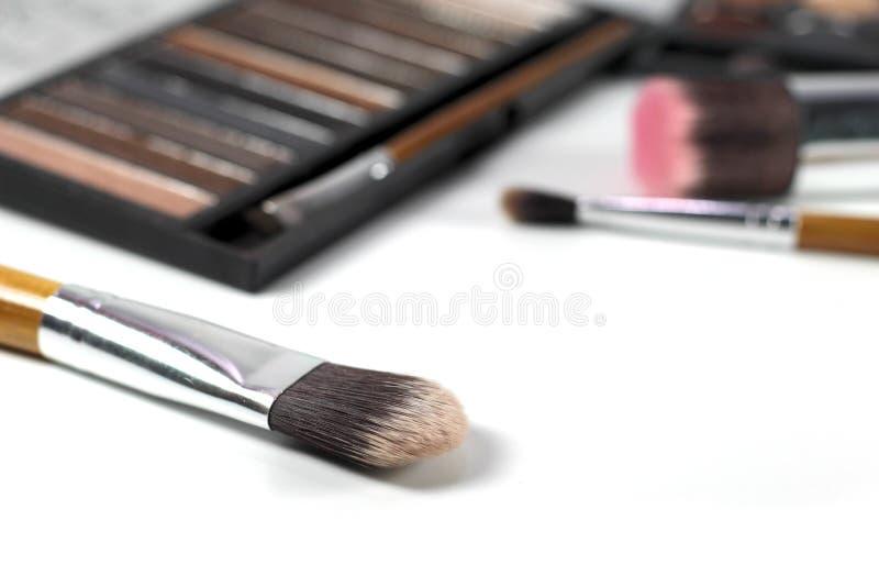 Fermez-vous vers le haut des brosses de maquillage avec la palette de fards à paupières et le fond de brosses image libre de droits