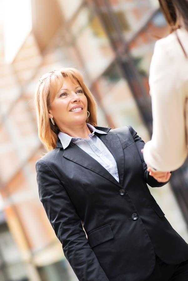 Fermez-vous vers le haut des couples d'affaires se serrant la main en dehors de buildin de bureau photos stock