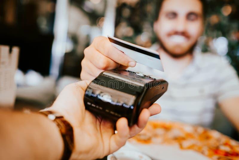 Fermez-vous vers le haut des détails de paiement par carte de crédit sans contact au restaurant Main de client payant avec la car photographie stock