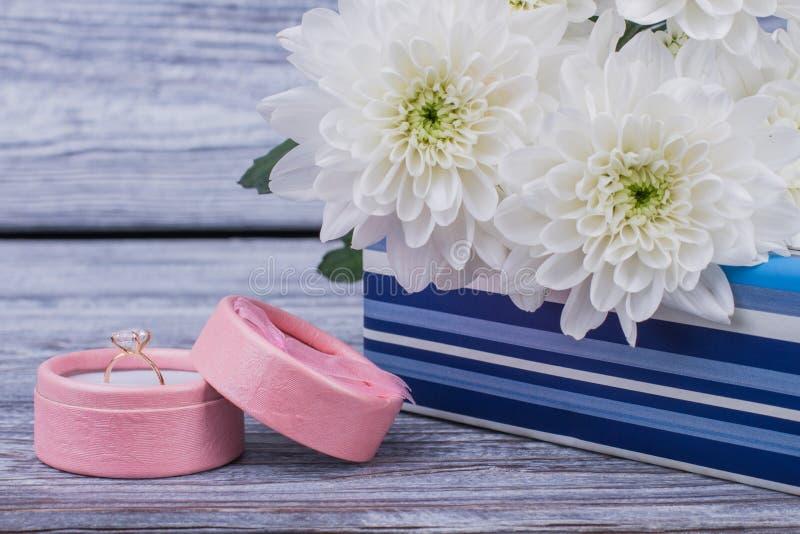Fermez-vous vers le haut des fleurs et du boîte-cadeau avec la bague à diamant image stock
