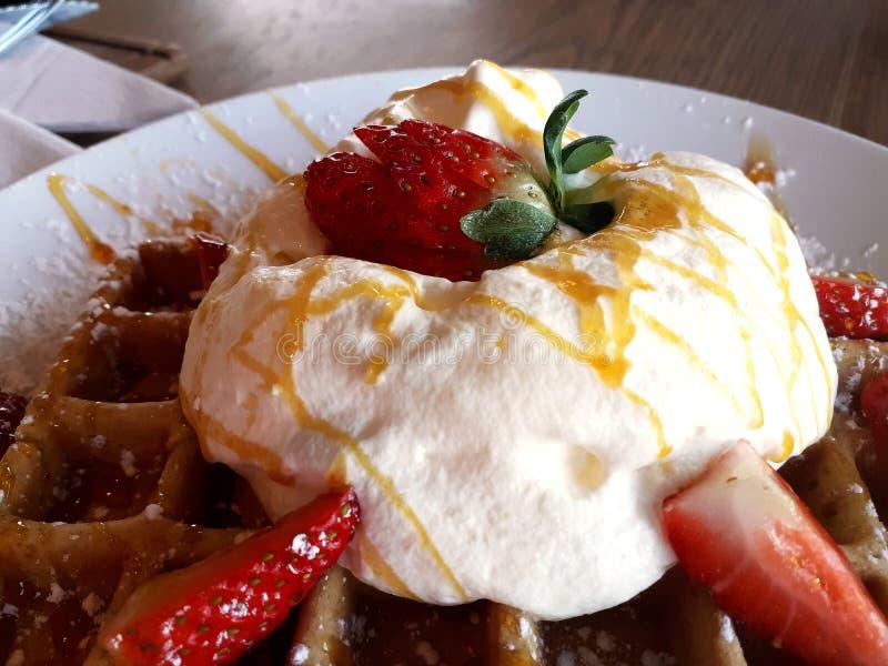Fermez-vous vers le haut des gaufres avec de la crème et des fraises du plat blanc photo stock