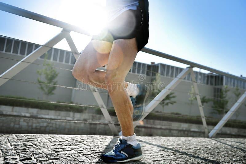 Fermez-vous vers le haut des jambes et des chaussures du fonctionnement de pratique de jeune homme sportif dans le contre-jour en images stock
