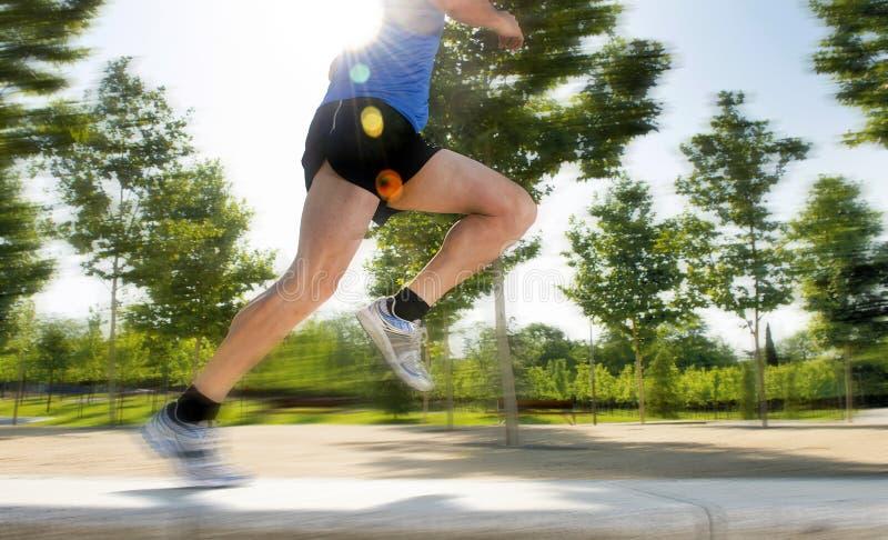 Fermez-vous vers le haut des jambes sportives du jeune homme fonctionnant en parc de ville sur la formation d'été dans le concept image stock