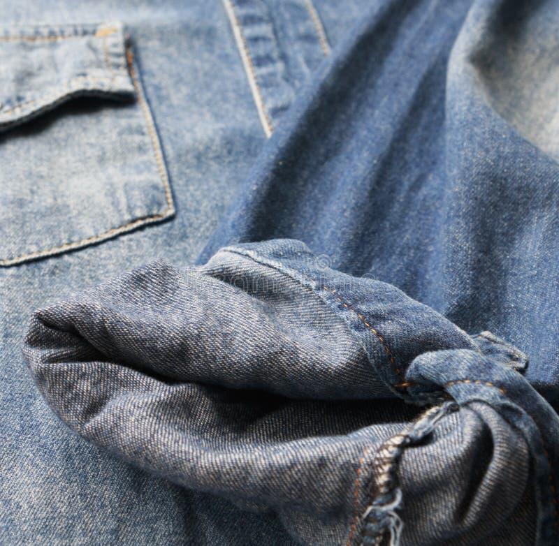 Fermez-vous vers le haut des jeans bleus de chemise de denim photos stock