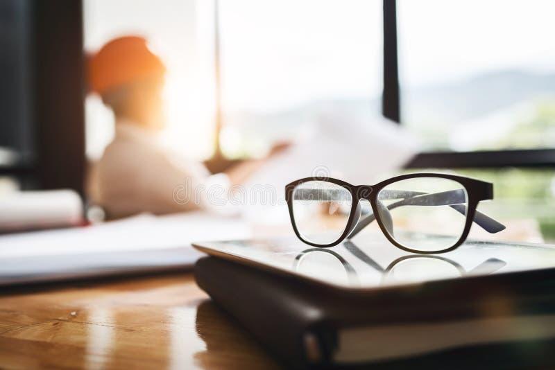 Fermez-vous vers le haut des lunettes sur un livre de planificateur de maison d'engi d'architecte photos stock