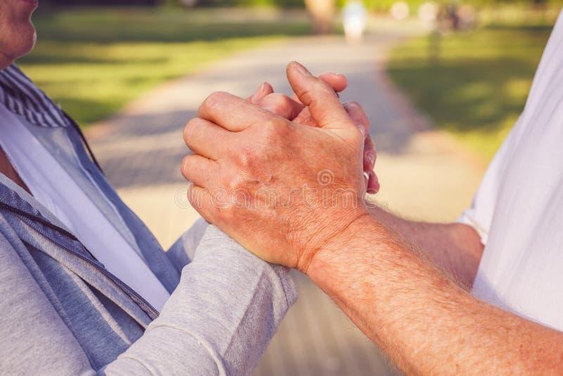 Fermez-vous vers le haut des mains des couples supérieurs pendant la promenade en parc photographie stock