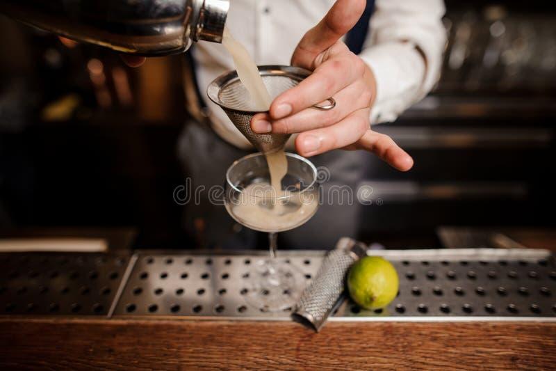Fermez-vous vers le haut des mains de barmans avec le cocktail images stock