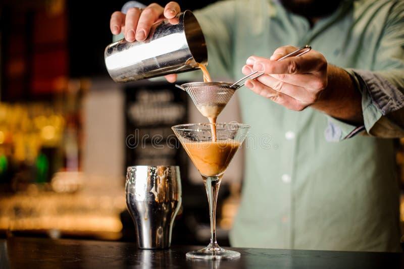 Fermez-vous vers le haut des mains de barmans avec le cocktail photo libre de droits