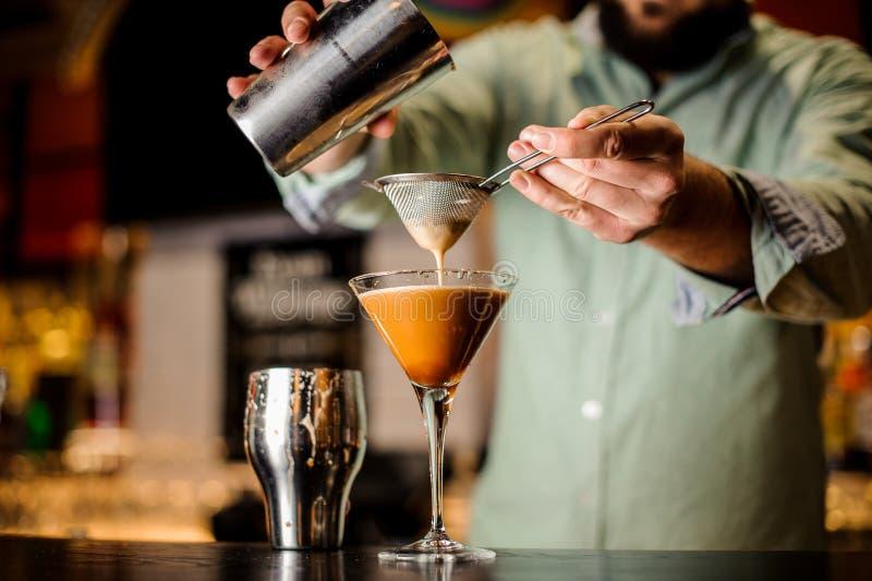 Fermez-vous vers le haut des mains de barmans avec le cocktail de café images libres de droits