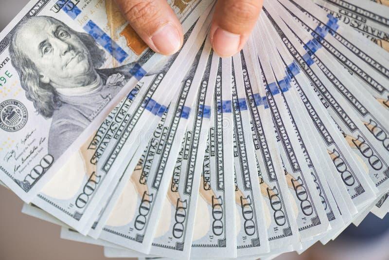 Fermez-vous vers le haut des mains de femme tenant des factures de dollar US images stock