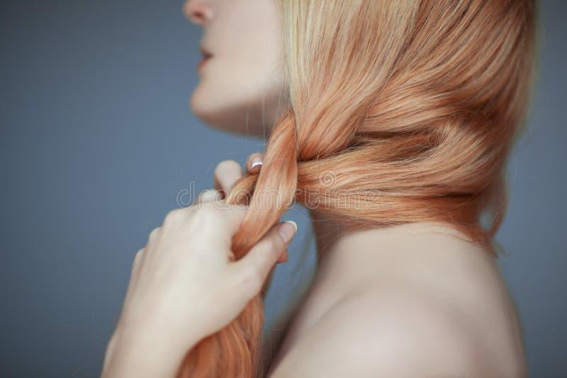 Fermez-vous vers le haut des mains de femme tressant des cheveux, regard sensuel photographie stock