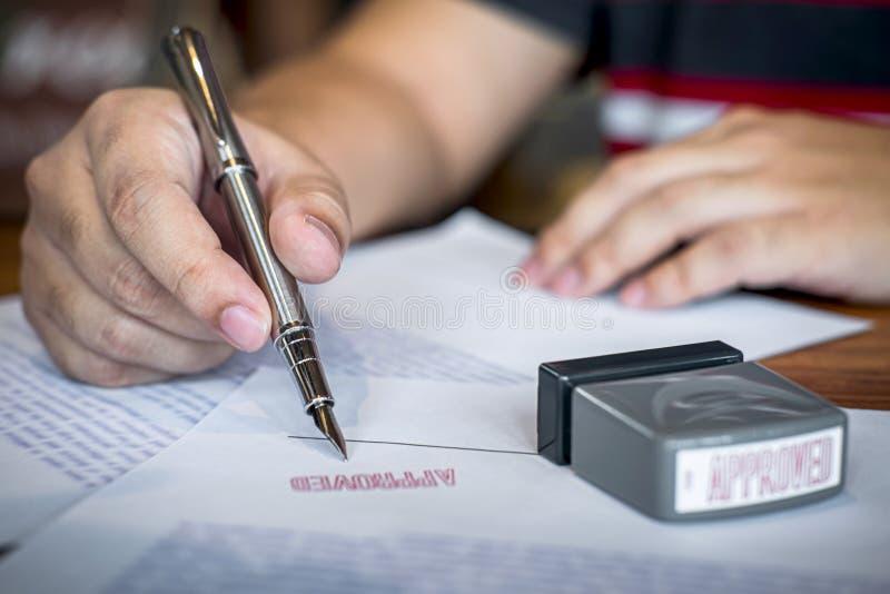 Fermez-vous vers le haut des mains de la signature et du timbre d'homme d'affaires sur le document sur papier pour approuver l'ac photo libre de droits