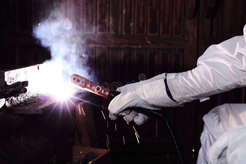 Fermez-vous vers le haut des mains de soudeuse d'artisan avec de l'acier en métal de soudure de torche et de gants protecteurs av image libre de droits