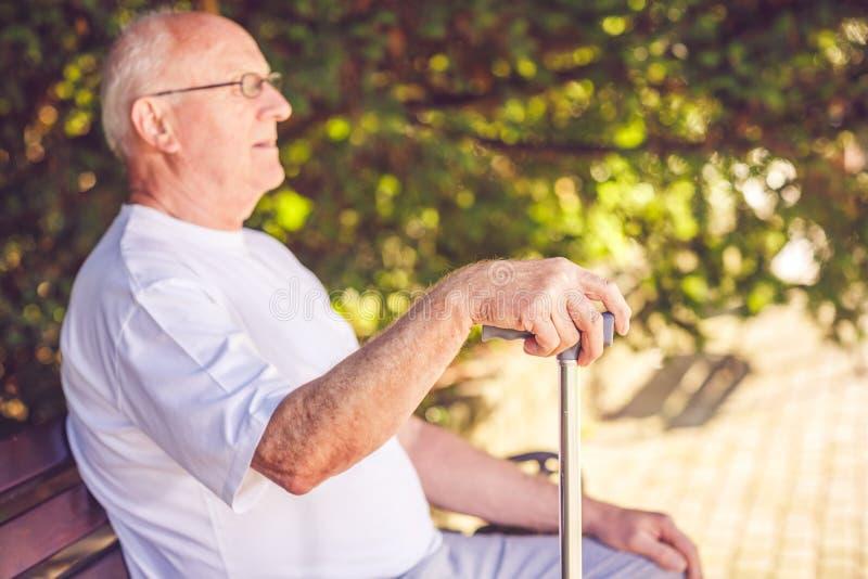 Fermez-vous vers le haut des mains de vieil homme avec son bâton de marche photographie stock libre de droits