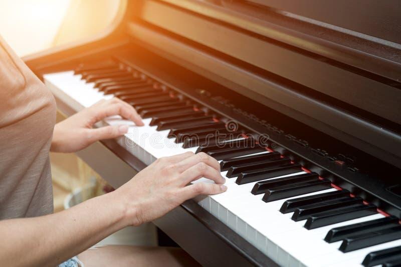 Fermez-vous vers le haut des mains femelles sur le piano de corde images libres de droits
