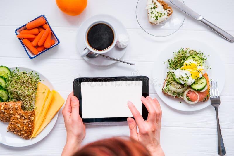 Fermez-vous vers le haut des mains femelles tenant le comprimé avec l'écran vide de l'espace de copie et ayant le petit déjeuner  photos stock
