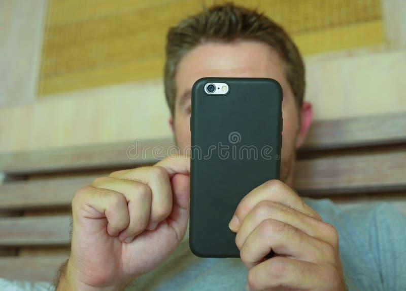 Fermez-vous vers le haut des mains tenant le téléphone portable de la chambre à coucher de jeune homme à la maison utilisant le m image libre de droits
