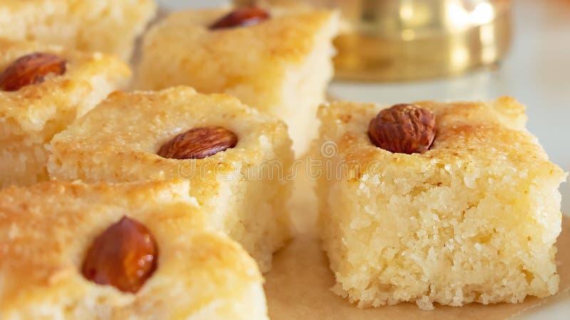 Fermez-vous vers le haut des morceaux Basbousa ou du gâteau arabe traditionnel de semoule de namoora avec l'écrou d'amande et vou images stock