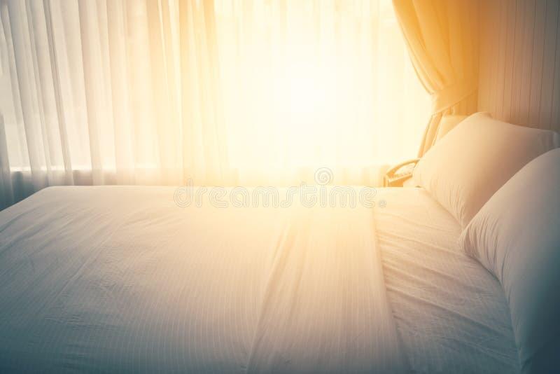 Fermez-vous vers le haut des oreillers sur le drap dans la chambre à coucher avec l'effet de configuration du soleil, rétro style photographie stock