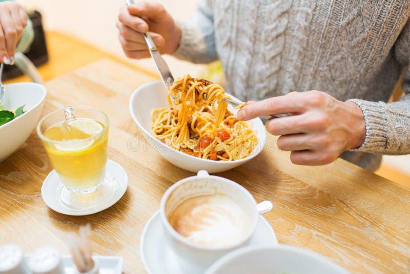 Fermez-vous vers le haut des pâtes mangeuses d'hommes pour le dîner au restaurant photographie stock