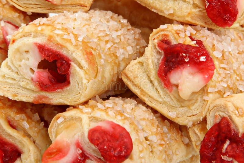 Fermez-vous vers le haut des pâtisseries remplies par framboise avec arrose images stock