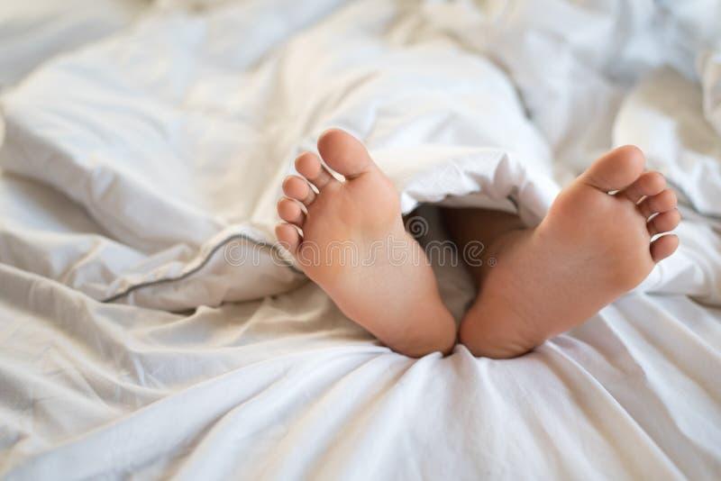 Fermez-vous vers le haut des pieds d'enfant en bas âge dormant sur le lit photographie stock libre de droits