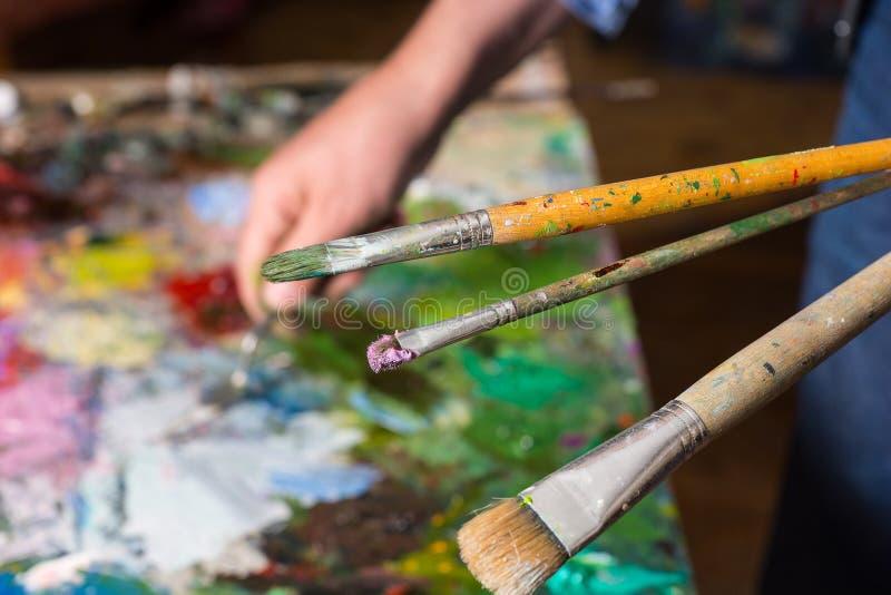 Fermez-vous vers le haut des pinceaux dans le painter& x27 ; main de s photo stock