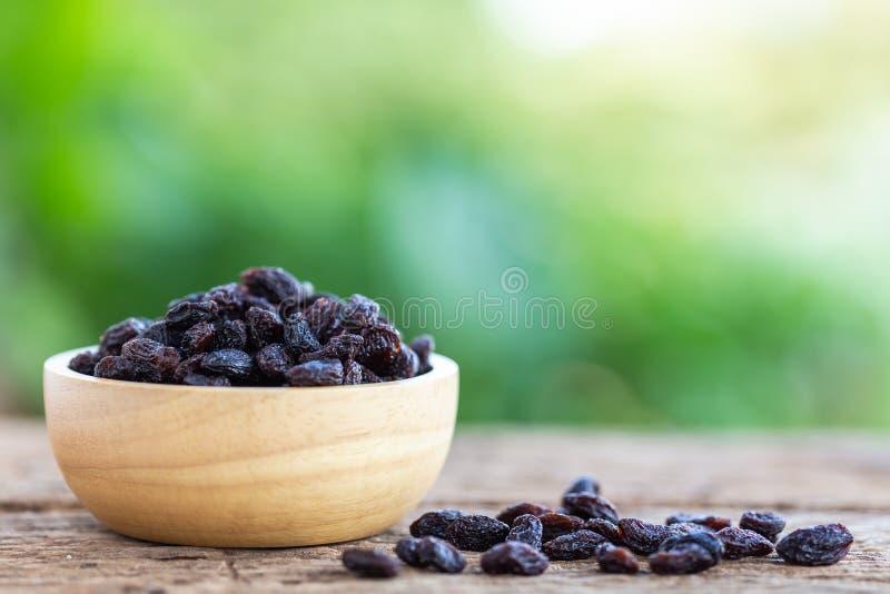 Fermez-vous vers le haut des raisins secs dans la cuvette sur le fond en bois de table photo stock