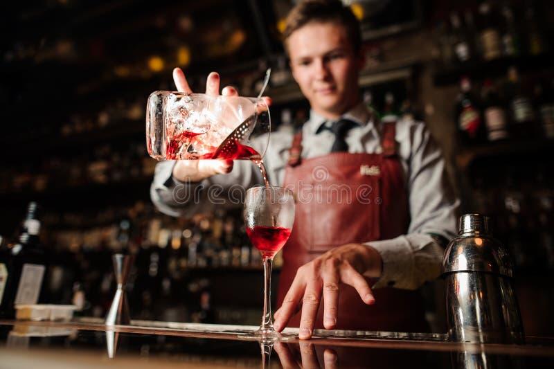 Fermez-vous vers le haut du barman versant le cocktail rouge lumineux d'alcool dans le verre de fantaisie photo libre de droits