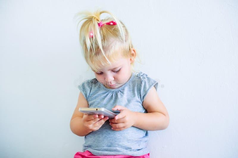 Fermez-vous vers le haut du beau petit bébé se tenant et jouant avec le téléphone intelligent sur le fond blanc de mur Enfants et images libres de droits