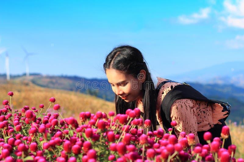 Fermez-vous vers le haut du bonheur caucasien de femme et d'expression, jolie fille avec les fleurs roses de Gomphrena photographie stock libre de droits