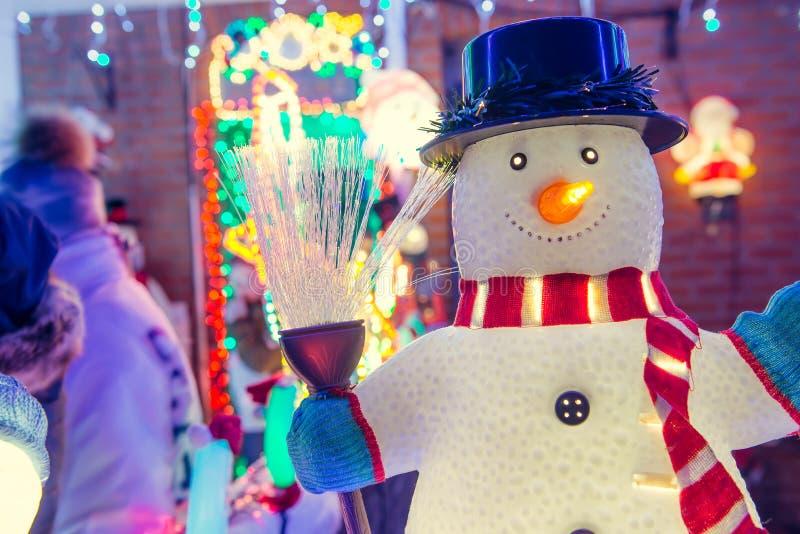 Fermez-vous vers le haut du bonhomme de neige décoratif avec des lumières et des décorations extérieures brillantes de Noël la nu image libre de droits