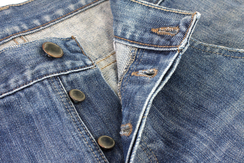 Fermez-vous vers le haut du bouton en métal sur des jeans images stock