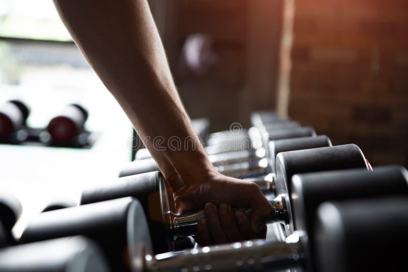 Fermez-vous vers le haut du bras musculaire Main d'homme tenant l'haltère images stock