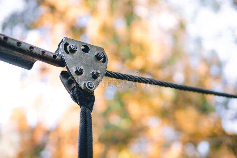 Fermez-vous vers le haut du câble de sécurité, montant la vitesse en parc d'aventure sont occupés à escalade ou passer des obstac photographie stock libre de droits