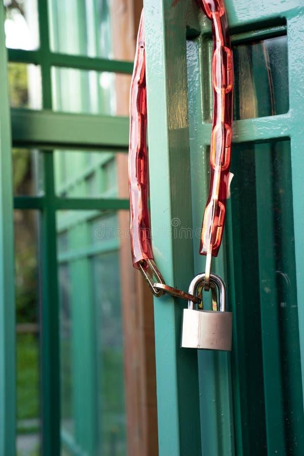 Fermez-vous vers le haut du cadenas et enchaînez dans la couverture en plastique accrochant sur le doo vert photos stock