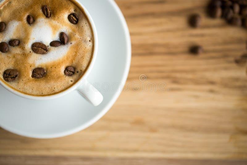 Fermez-vous vers le haut du café de tasse d'art de Latte avec des grains de café images stock