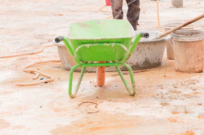 fermez-vous vers le haut du chariot et des travailleurs dans la construction de lieu de travail image stock