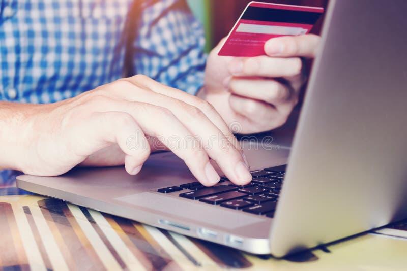 Fermez-vous vers le haut du clavier de dactylographie d'ordinateur portable d'homme de main et de tenir la carte de crédit image libre de droits