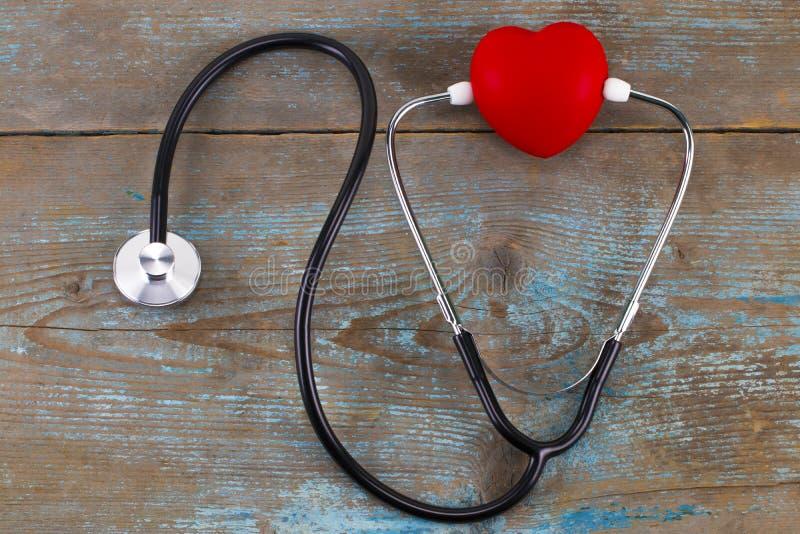 Fermez-vous vers le haut du coeur et du stéthoscope rouges sur la table en bois, la santé d du monde photos stock