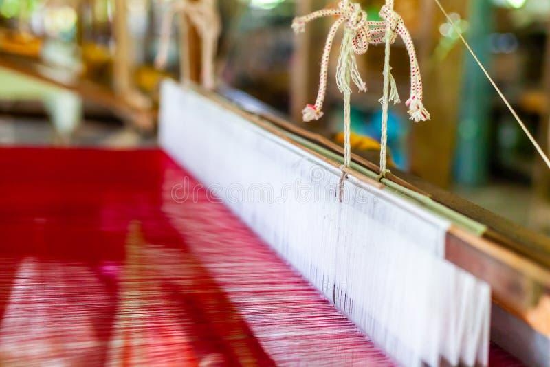 Fermez-vous vers le haut du coton tissé par main Weaver Machine Loom avec la soie rouge thr images stock