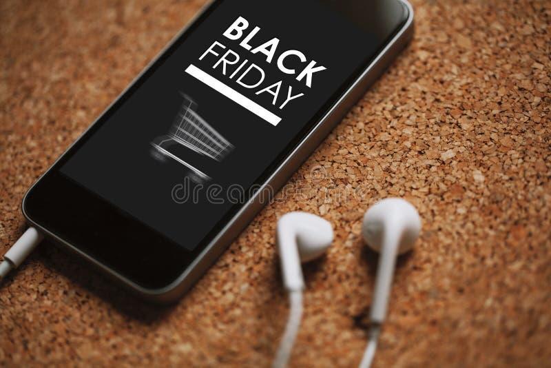 Fermez-vous vers le haut du détail du téléphone portable avec la conception de vente de Black Friday dans l'écran, les écouteurs  photographie stock libre de droits