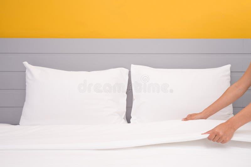 Fermez-vous vers le haut du drap blanc installé par main dans la chambre d'hôtel, foyer sélectif photographie stock