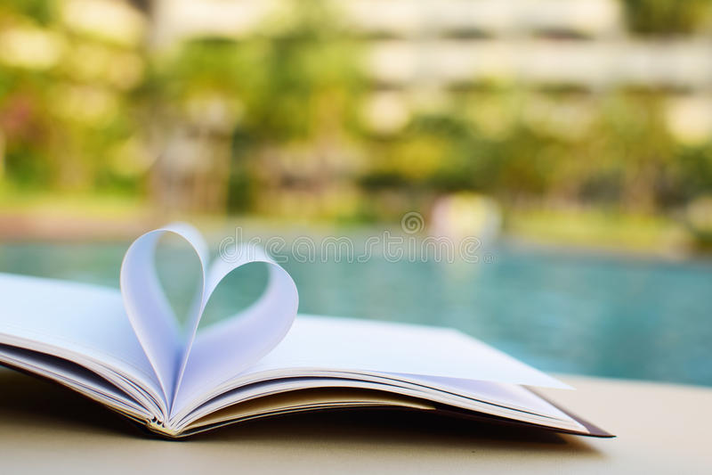 Fermez-vous vers le haut du livre de coeur sur la table et de la piscine avec le fond de tache floue de filtre de vintage photographie stock