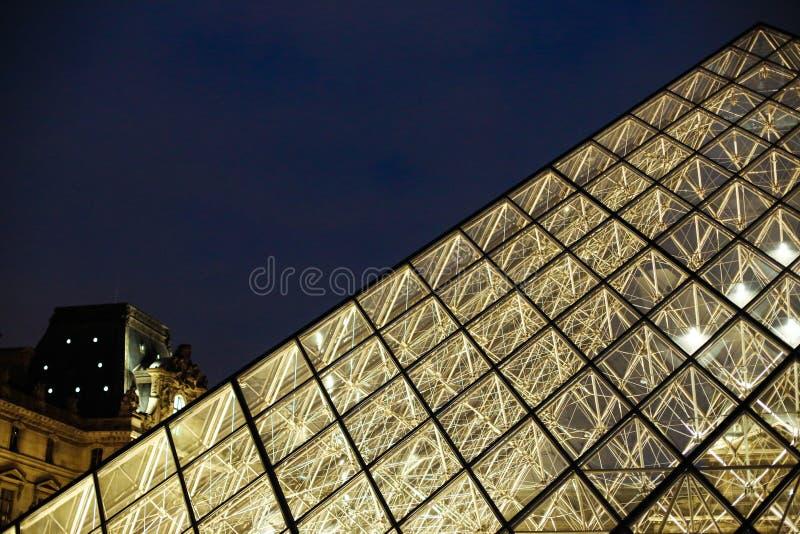 Fermez-vous vers le haut du Louvre stupéfiant la pyramide en verre dans la nuit Paris, France images libres de droits