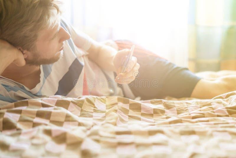 Fermez-vous vers le haut du media social de réseau de contrôle dans le téléphone se situant dans le lit, réveillez juste f photos stock