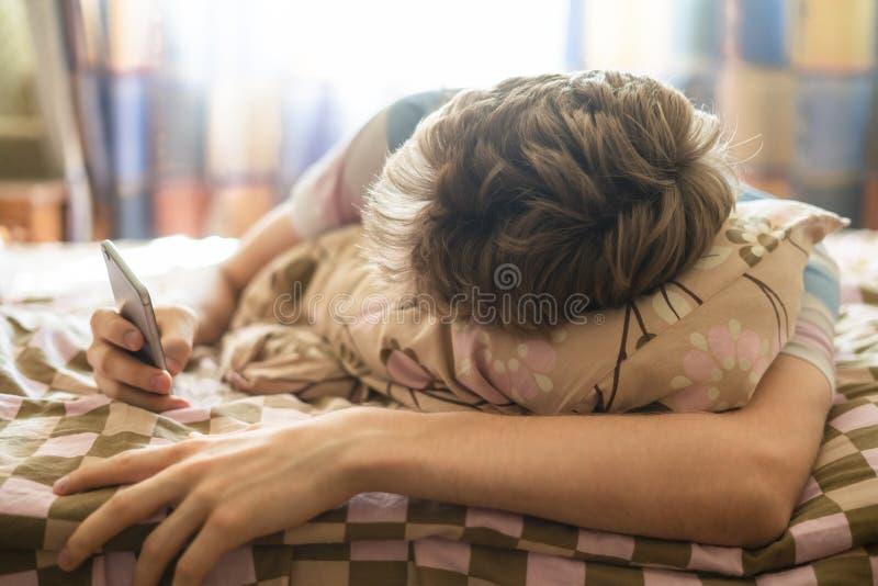 Fermez-vous vers le haut du media social de réseau de contrôle dans le téléphone se situant dans le lit, réveillez juste f images stock