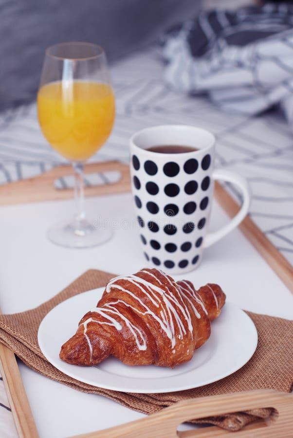 fermez-vous vers le haut du petit déjeuner dans le lit Nourriture blanche de café et de chocolat de croissants Tasse de coffe ou  images stock