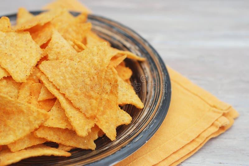 Fermez-vous vers le haut du plat avec des Nachos avec du fromage Serviette et Gray Rustic Table oranges image libre de droits